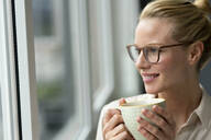 Young businesswoman with cup of coffee looking out of window - JOSF03531