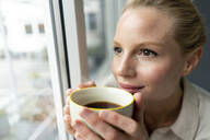 Young businesswoman with cup of coffee looking out of window - JOSF03534