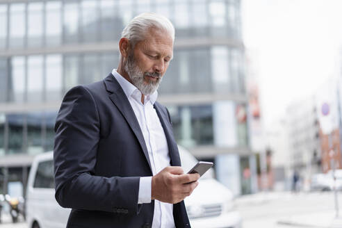 Mature businessman using cell phone in the city - DIGF07422