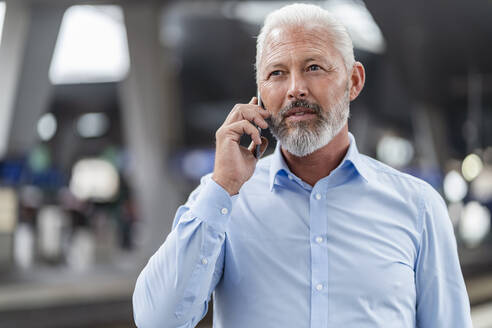 Mature businessman talking on cell phone at the station platform - DIGF07470
