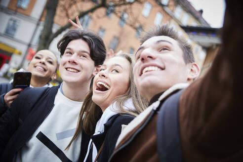 Cheerful teenage boys and girls enjoying in city during weekend - MASF12837