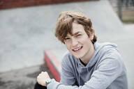 Portrait of smiling teenage boy wearing hooded shirt while sitting on sidewalk in city - MASF12900