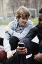 Teenage boy looking at friend's mobile phone while sitting on sidewalk after basketball practice - MASF12906