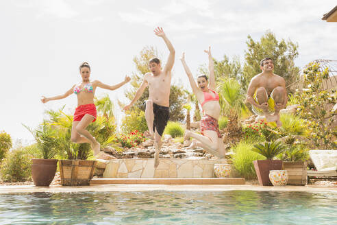Friends jumping into swimming pool - BLEF09719
