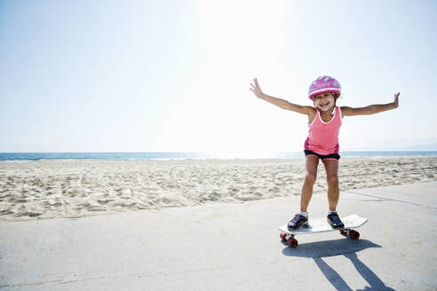 Girl riding skateboard at beach - BLEF09731
