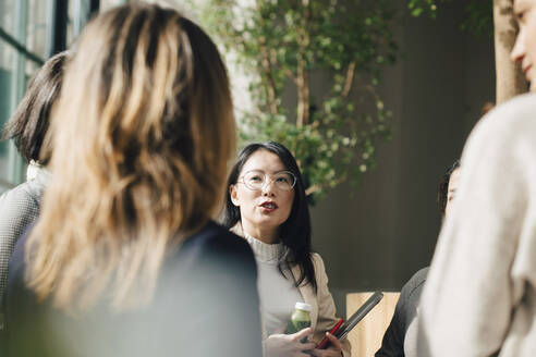 Female professional discussing with coworkers in meeting at conference event - MASF12975