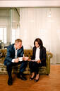 Manager explaining business opportunities to female colleague on sofa in office - MASF13041