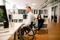 Disabled male professional sitting on wheelchair while smiling businesswoman using laptop at work place - MASF13050