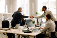 Businessmen shaking hands during sales meeting in office - MASF13053