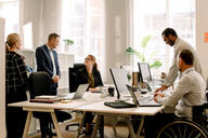 Business professionals working together at desk in office - MASF13056