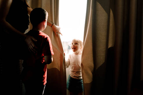 Girl standing by window looking at mother with boy in hotel room - MASF13077