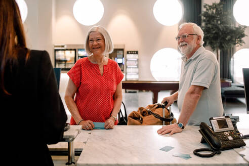 Smiling senior couple talking to receptionist in hotel - MASF13095
