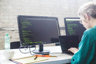 Side view of businesswoman working on start-up project while coding in office - MASF13110