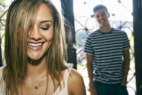 Woman laughing with boyfriend in background - BLEF09743