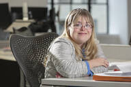Caucasian businesswoman with Down Syndrome smiling in office - BLEF09824