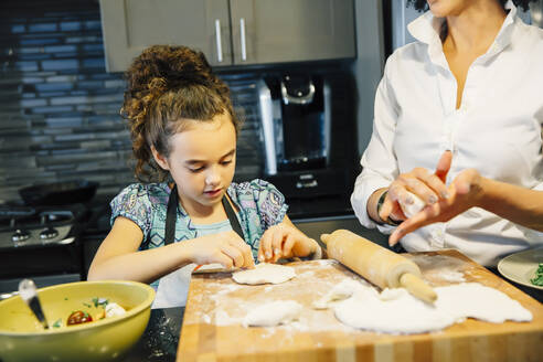 Mother and daughter baking in kitchen - BLEF09833