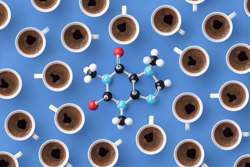 Directly above view of caffeine chemical formula with coffee cups over blue background - DRBF00159