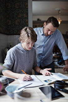 Father looking at son doing homework on table - MASF13122