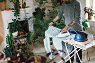 Man ironing his shirt on board in room at home - MASF13149
