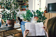 Full length of mid adult woman reading book while relaxing at home - MASF13215