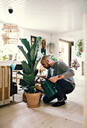 Man kneeling while watering potted plant at home - MASF13239