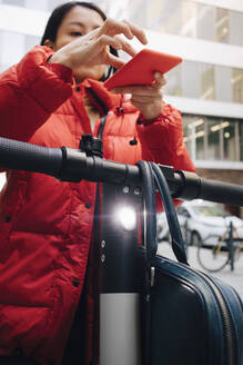 Female commuter scanning QR code on electric push scooter handlebar with smart phone - MASF13254