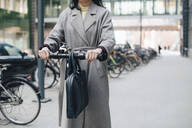 Midsection of businesswoman riding electric push scooter on footpath in city - MASF13257