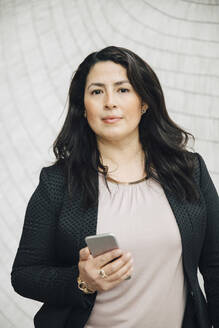 Portrait of confident businesswoman holding smart phone standing against wall at office - MASF13284