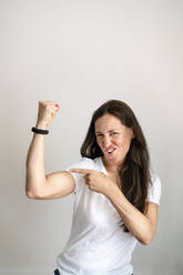 Portrait of cheerful mature woman pointing at bicep against white background - DMOF00185