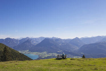 Rear view of senior male hiker sitting on bench while looking at Dachstein Mountains against blue sky - GWF06174