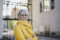 Portrait of mature woman with grey hair wearing glasses and yellow clothes - KNSF06114