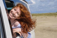 Portrait of carefree redhead teenage girl with head out of car window at beach against sky - LBF02624
