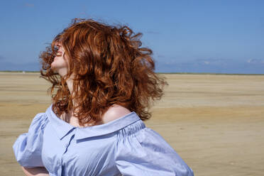 Carefree teenage girl tousled hair standing at beach against sky on sunny day - LBF02630