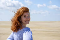 Smiling teenage girl looking over shoulder while standing at beach against sky on sunny day - LBF02633