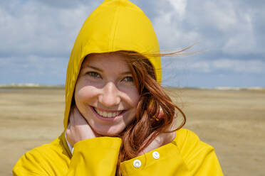 Close-up portrait of redhead teenage girl wearing yellow raincoat while standing at beach against sky on sunny day - LBF02636
