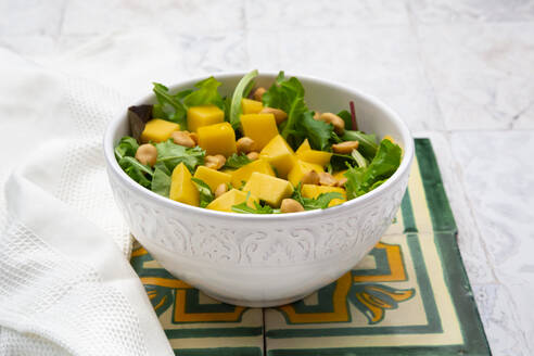 High angle view of fresh salad in bowl by napkin on tiled floor - LVF08173