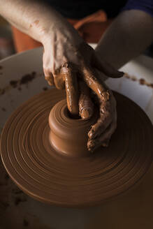Potter forming clay on a wheel - ABZF02405