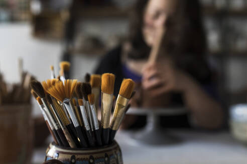 Potter shaping clay in studio, brushes in the foreground - ABZF02420