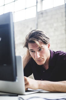 Young male entrepreneur working on start-up project while coding at desk in office - MASF13321