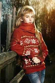 Caucasian girl leaning on fence - BLEF09846