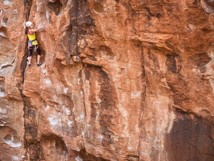 Mixed race girl rock climbing on cliff - BLEF09960