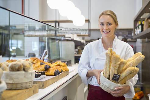 Smiling baker holding basket of bread in bakery - JUIF02381