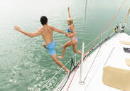 Couple jumping from sailboat deck into ocean - BLEF10034