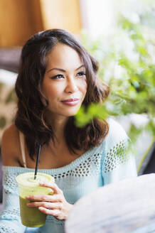 Close up of Chinese woman drinking smoothie - BLEF10100