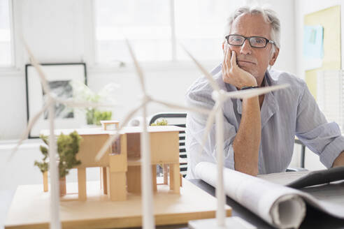 Older Caucasian architect examining scale model in office - BLEF10112