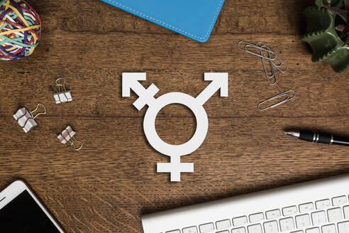 View from above transgender symbol on wooden desk - FSIF04111