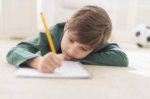 Hispanic boy doing homework on floor - BLEF10208