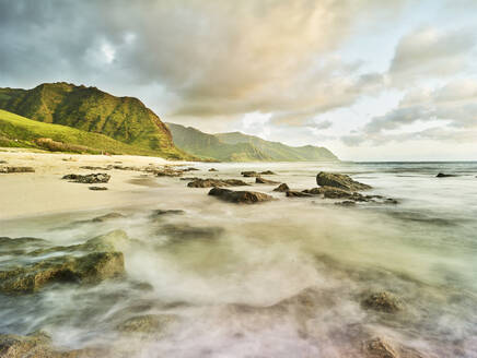 Scenic view of waves splashing on shore at beach in Ka'ena Point State Park against sky - CVF01278