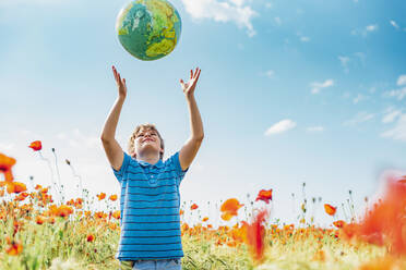 Boy catching globe while standing in poppy field against sky on sunny day - MJF02386