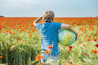 Rear view of boy holding globe in poppy field on sunny day - MJF02392